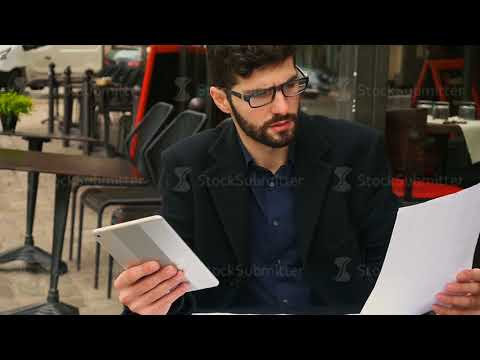 Graphic designer working with tablet and papers at cafe table in slow motion