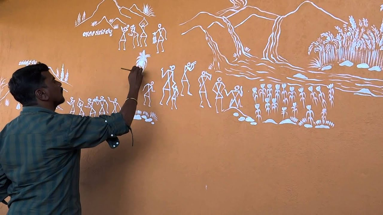 An artist painting a beautiful Warli Art painting on the ...