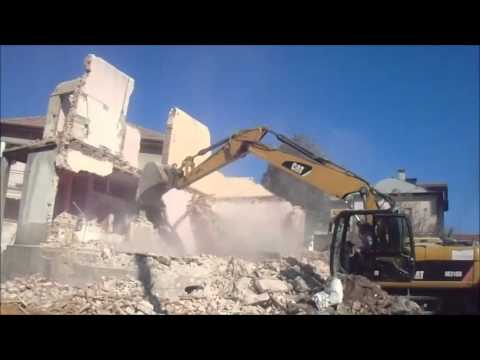 Cat M318D demolishing a old  building from bricks