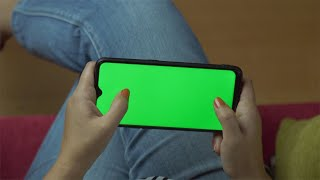 Closeup of female hands holding a green screen smartphone in landscape mode