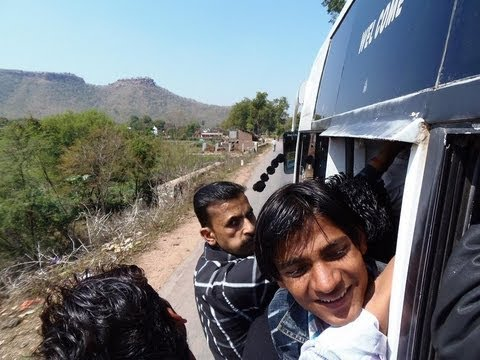 Men hanging off a moving bus in India