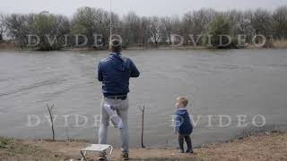Fisherman spinning fishing reel during biting in river. Father fishing with son