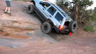 jeep grand cherokee wj climbing a steep slab moab ut
