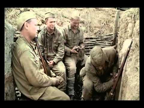Сидят в окопе солдаты во время войны, отстреливаются. Один