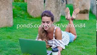 Young girl student lies on grass with laptop In the break between lessons. She drinks coffee from