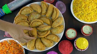 Woman hands picking delicious Gujiya's while celebrating the Holi festival in India