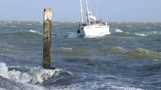 Zeiljacht vaart bij harde wind de haven van Vlieland binnen