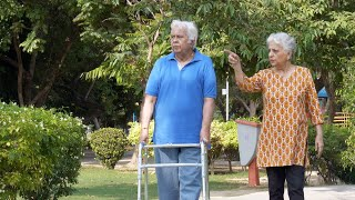 Retired old man doing a morning walk using a walker with his wife in a garden