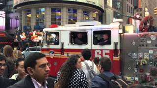 FDNY ENGINE 65 CRUISING BY ON WEST 42ND STREET IN TIMES SQUARE AREA OF MANHATTAN IN NEW YORK CITY.