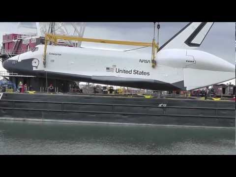 SPACE SHUTTLE ENTERPRISE HOISTED ON A BARGE