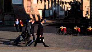 Business men walking with luggage through a plaza in Bologna Italy.