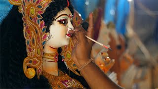 Tilt shot of an Indian artist painting eyes of a sculpture of Ma Durga for Durga Puja