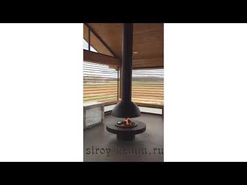 Круглый островной камин в деревянном доме