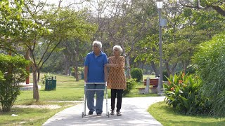 Happy old couple enjoying a Sunday morning walk in a hospital park - lifestyle couples