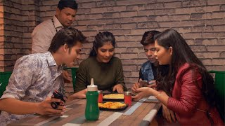 Indian waiter serves a delicious pizza to a group of young and hungry friends in a cafe