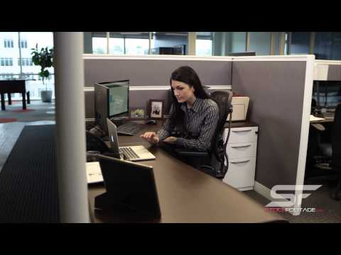 Woman in cubicle working on computer and looking at laptop.