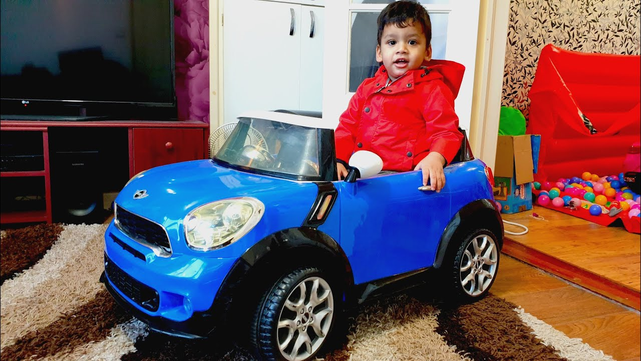 Little boy playing with blue mini Cooper