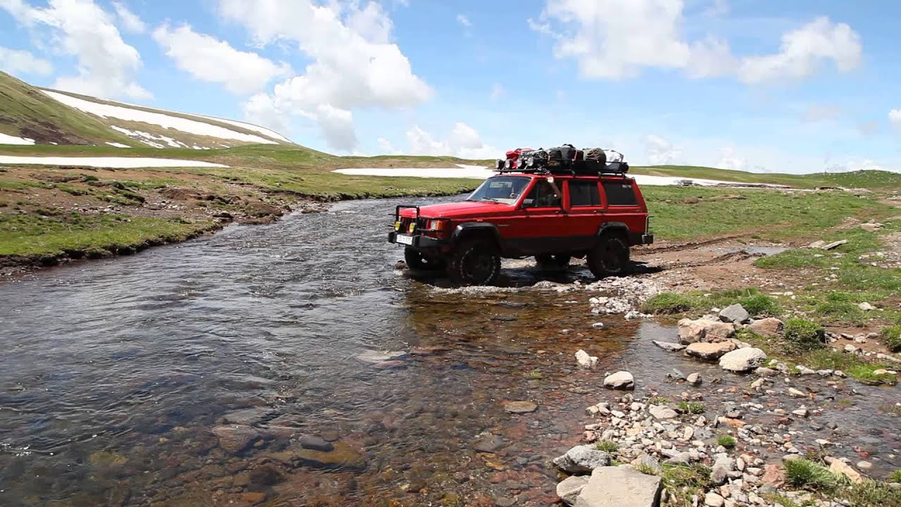 Jeep cherokee xj passing mountain river