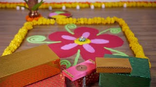 Tilt shot of a colorful rangoli with Diwali Diya and gift boxes - decoration for Diwali festival
