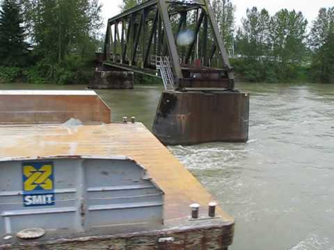 Tug boat pulling barge up Fraser river through Mission bc rail bridge