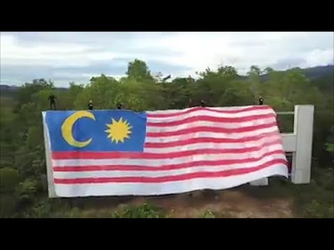 Youths drape giant Jalur Gemilang over iconic 'Ipoh' sign