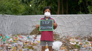 "A young child standing with a signboard of ""Stop Pollution"" while wearing a medical mask"
