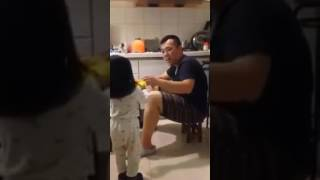 A little girl giving her dad toilet water