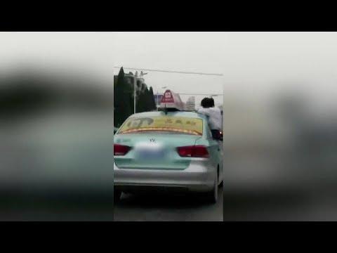 Chinese schoolgirl caught doing homework on top of speeding taxi