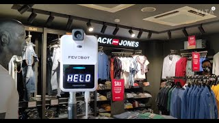 Fevobot Automatic Infrared (IR) wall-mounted thermometer installed at a garment showroom | Fevo