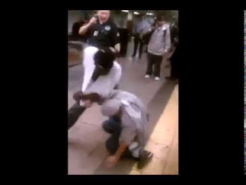 2 Men fight in a Brooklyn NY Train Station. Cop just looks on.