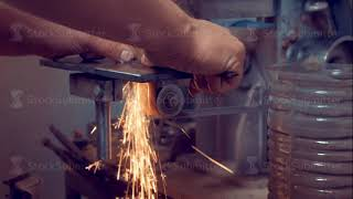 Man using metalworking equipment for processing and sharpening metal on factory