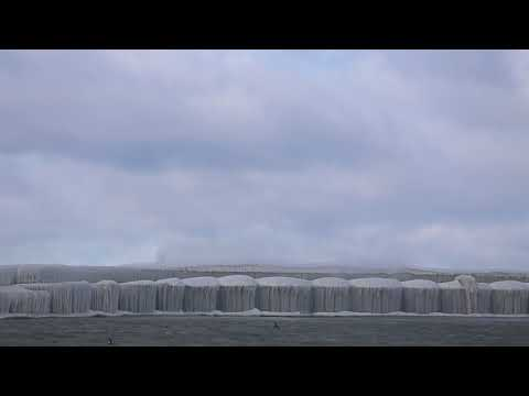 Waves crash against Port Austin breakwater (shot from behind)