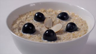 Pieces of almonds falling into a ceramic bowl full of oats, milk, and black grapes