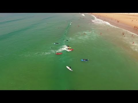 Group Surfing Lesson on Costa Caparica Beautiful Ocean Beach, Portugal. Aerial View | Stock Footage