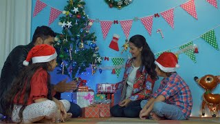 Happy Indian family of four sitting together in a decorated room on Christmas Eve