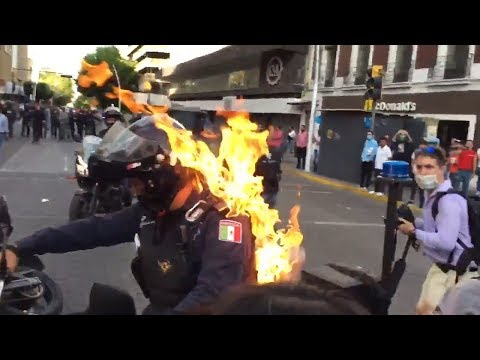 Rioter Douses Police Officer, Sets Him on Fire as Unrest Spreads Across Globe