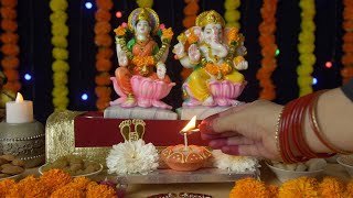 Shot of an Indian female's hand lighting up a Diya in front of Ganesh Ji and Laxmi Ji on Diwali