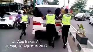 Anggota Satlantas Polresta Yogyakarta mendorong  Mobil mogok
