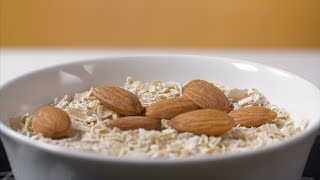 Closeup shot of almonds falling into a white bowl full of oats - healthy breakfast