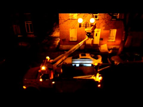 MONTREAL CITY WORKER FIXING STREET LIGHT WITH INTERNATIONAL UTILITY TRUCK