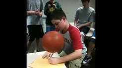 Scott spinning a basketball while writing his name