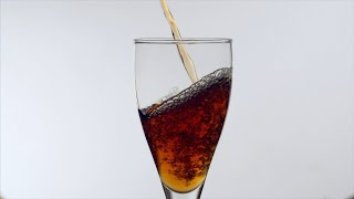 Slow motion shot of wine / black tea / coke / pepsi being poured into a glass