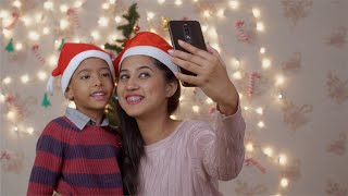 Indian mother and son taking a selfie near Christmas tree