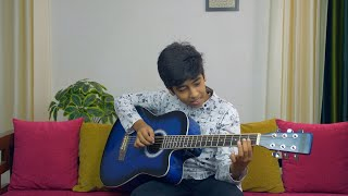 Handsome young musician playing the guitar while sitting on a sofa in his living room