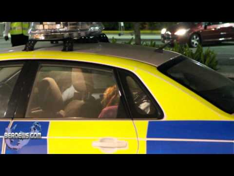 Suspected unruly passenger led away in a police car