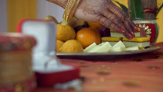 Closeup of mehndi on woman hands grabbing sweets during the wedding ceremony
