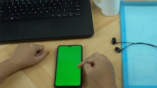 Woman hands using her smartphone with a green screen during office time in India