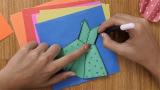 Girl decorating green coloured paper dress with sketch pen - Origami