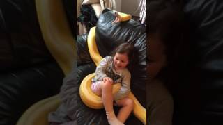 Little girl with a real snake on the couch python
