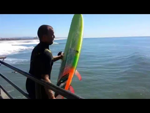 Johnny Denney Jumps Off Huntington Beach Pier To Surf